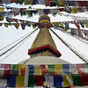 The temple stupa of Bodhnath (Boudha), with the iconic Buddha eyes. Colorful prayer flags surround the stupa.