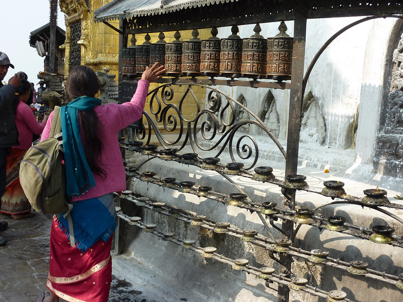 A pilgrim spinning the prayer wheels at the Swayambhunath Temple as she circumnavigates it clockwise as a part of the prayer ritual.  The temple is commonly referred to as the Monkey Temple given the monkeys that live on the compound.