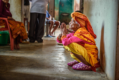 Elderly woman prays in a local retirement home, Nepal