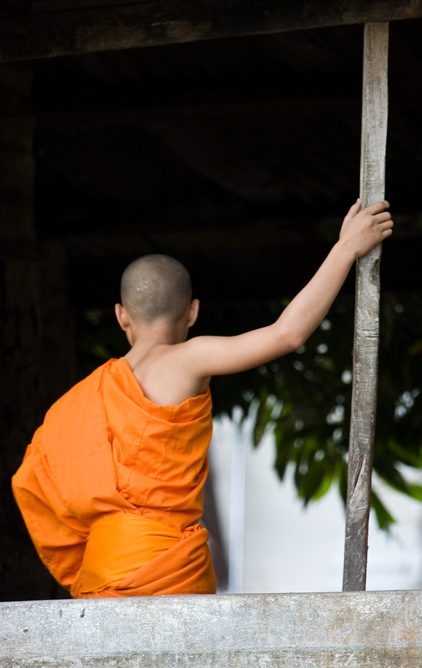 A monk leans against a pole in a monastery.<br /> <br /> Location: Luang Prabang, Laos<br /> <br /> Lens used: 100-400mm f4.5-5.6 IS