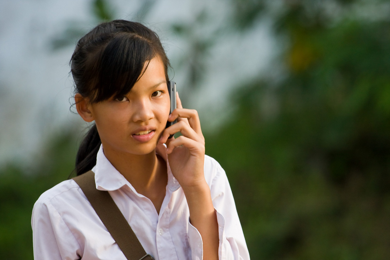 For teenagers here, like everywhere, the cell phone is a must-have accessory.<br /> <br /> Location: Luang Prabang, Laos<br /> <br /> Lens used: 100-400mm f4.5-5.6 IS