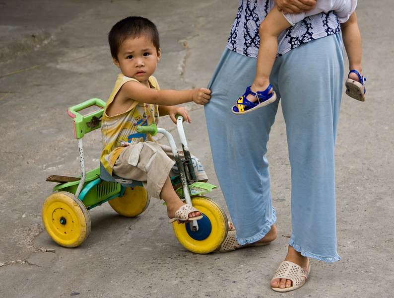 This tike on a trike wasn't too sure of my camera.  Good thing momma was there to protect him!<br /> <br /> Location: Ninh Binh, Vietnam<br /> <br /> Lens used: 24-105mm f4.0 IS