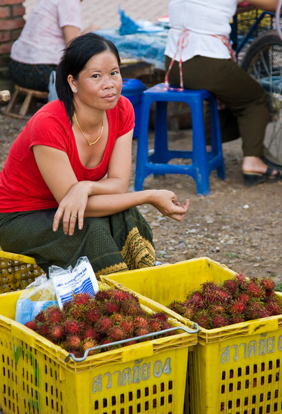 A woman sells rambutans at the small town market.<br /> <br /> Never had a rambutan before?  Their white slimy center with the mild taste contrasts to their wild exterior.  They're pretty common in tropical regions, but super exotic here in the continental US - expect to pay a high premium if you could find them at all.<br /> <br /> Location: Luang Nam Tha, Laos<br /> <br /> Lens used: 24-105mm f4.0 IS