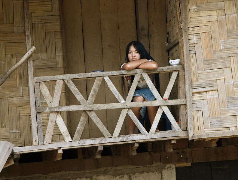 A teen-aged girl sits on her balcony, eyeing the buses and jeeps passing by.<br /> <br /> I was in one of said jeeps and shot this as we bounced and sped through her village.<br /> <br /> Location: Near Luang Nam Tha, Laos<br /> <br /> Lens used: 24-105mm f4.0 IS