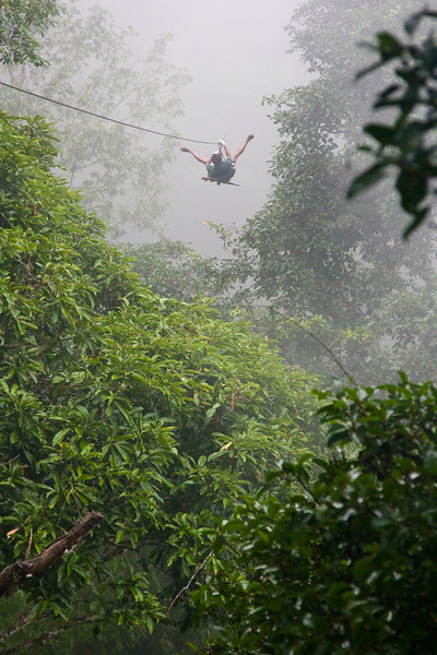Here, a 'forest ranger' zips away from Tree House #1 with his AK strapped to his back.  I'm trying to determine if his zipping into the fog asshole first was pure bravado or his way of passing a diss at the Fates or both.<br /> <br /> Location: Bokeo Forest Preserve, Laos<br /> <br /> Lens used: 24-105mm f4.0 IS