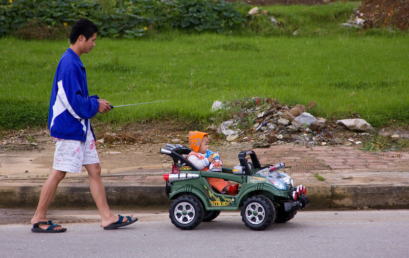 A man taking his son out for a walk.  I thought it rather ingenious, myself.<br /> <br /> Location: Sapa, Vietnam<br /> <br /> Lens used: 24-105mm f4.0 IS