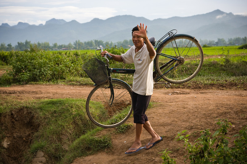 A local man throws a wave while he carries his bike across a ditch.<br /> <br /> Location: Dien Bien Phu, Vietnam<br /> <br /> Lens used: 24-105mm f4.0 IS