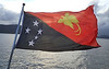 PNG flag, adopted July 1, 1971. Depicts the Southern Cross constellation and a raggiana bird-of-paradise. Chosen by national design competition which was won by then 15-year-old Susan Karike Huhume.