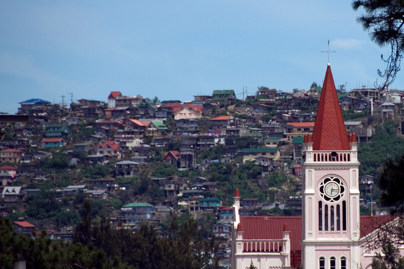 Baguio Cathedral tower with hillside villages on the background - Baguio, Philippines