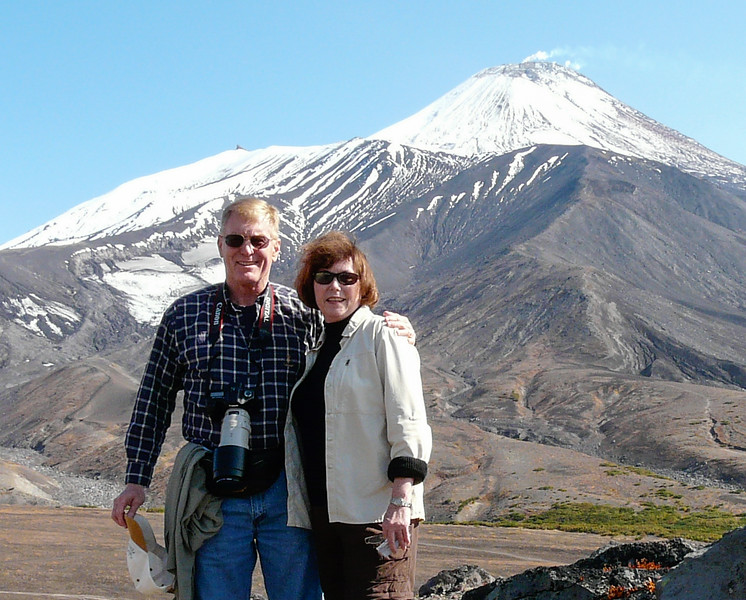 Boomer man and woman standing in front of a snow-capped volcano with smoke puffing out of the cone.