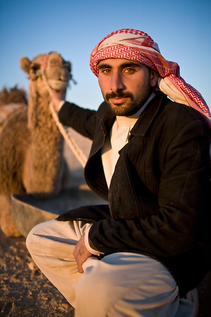 Palmyra, Syria - January, 2008: Portrait of a young Syrian Bedouin  man with his camel in the desert. (Photo by Christopher Herwig)