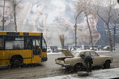 Tbilisi, Georgia - January, 2008:A old soviet car broken down on Rustavelis street in Tbilisi with  Fashion models advertising a new building construction in the background. (Photo by Christopher Herwig)