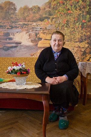 Tbilisi, Georgia - January, 2008: Portrait of a senior Georgian woman in front of large landscape picture. (Photo by Christopher Herwig)