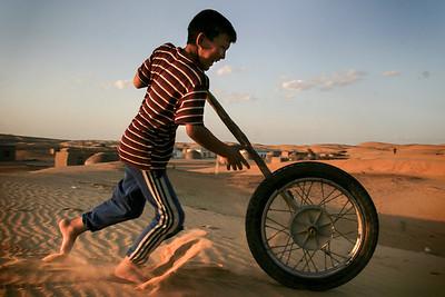 Turkmen boy pushing wheel in the desert