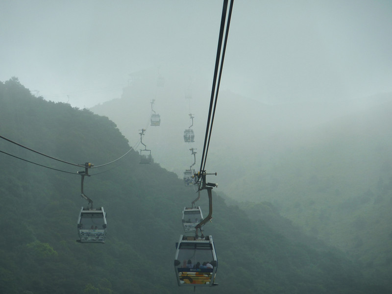 The cable car ride from the bottom of Lantau Island to the peak where Po Lin Monastary and the bronze Buddha are located is a breathtaking journey.  The summit is high, and you need to travel into the clouds. No, it's not smoke.