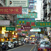 A busy urban street in the Kowloon side of Hong Kong.  Signs in Chinese dominate the street.
