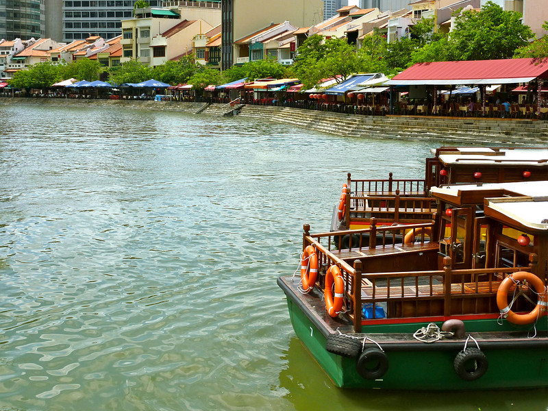 Old-fashioned bum boats at rest near the waterfront restaurants of Boat Quay in Singapore.