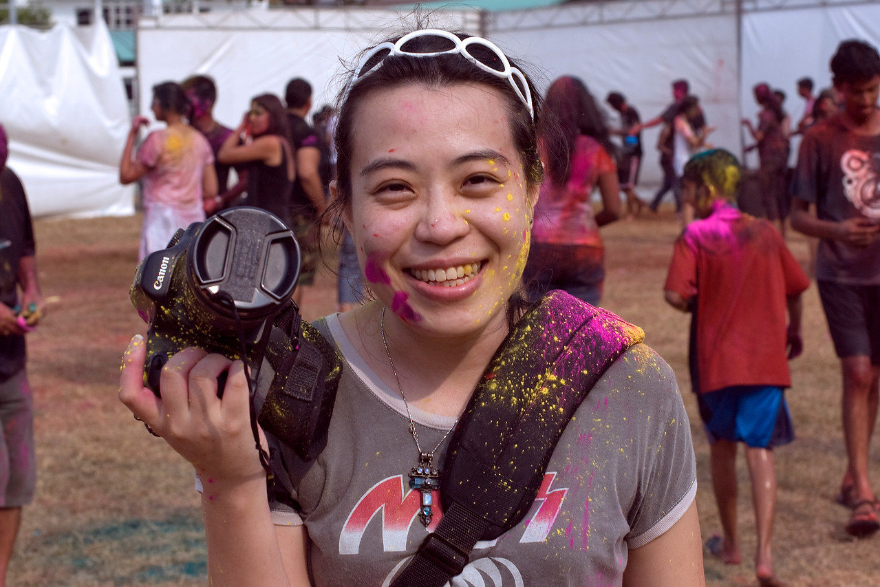 Female photographer splattered with colors at Singapore Holi Festival