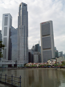 Restaurants on the south bank of the Singapore river with skyscapers in the background.
