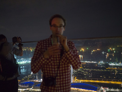 Dan drinking his sling with Singapore in the background