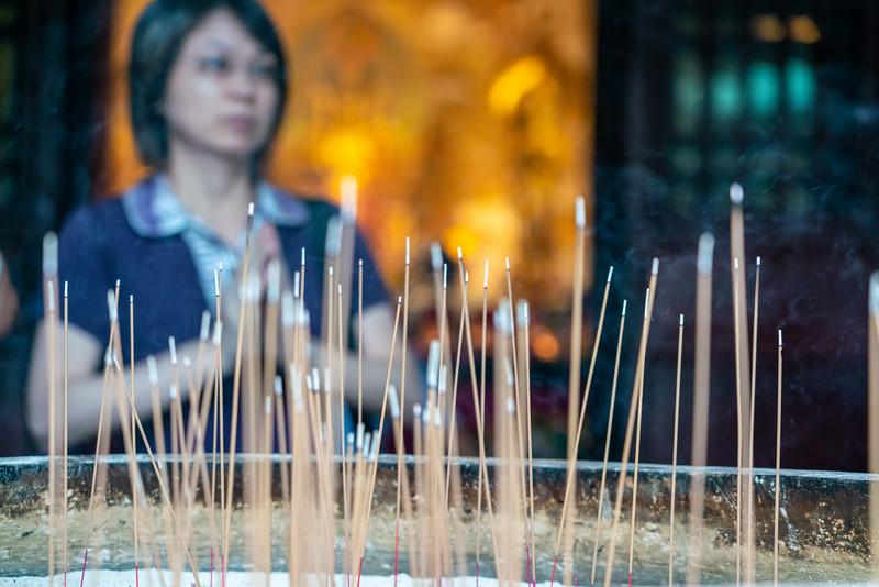 Woman burning incense and praying.