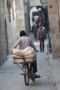 Aleppo, Syria - January, 2008: Man delivers flat bread on his bike in the narrow streets of Aleppo.  (Photo by Christopher Herwig)
