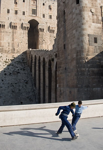 Aleppo, Syria - January, 2008: Young boys playing football outside the Citadel in downtwon Aleppo which was first built between 364-333 BC while the majority of the present day structure dates back to Mamluk rule between 1250-1517 AD. (Photo by Christopher Herwig)