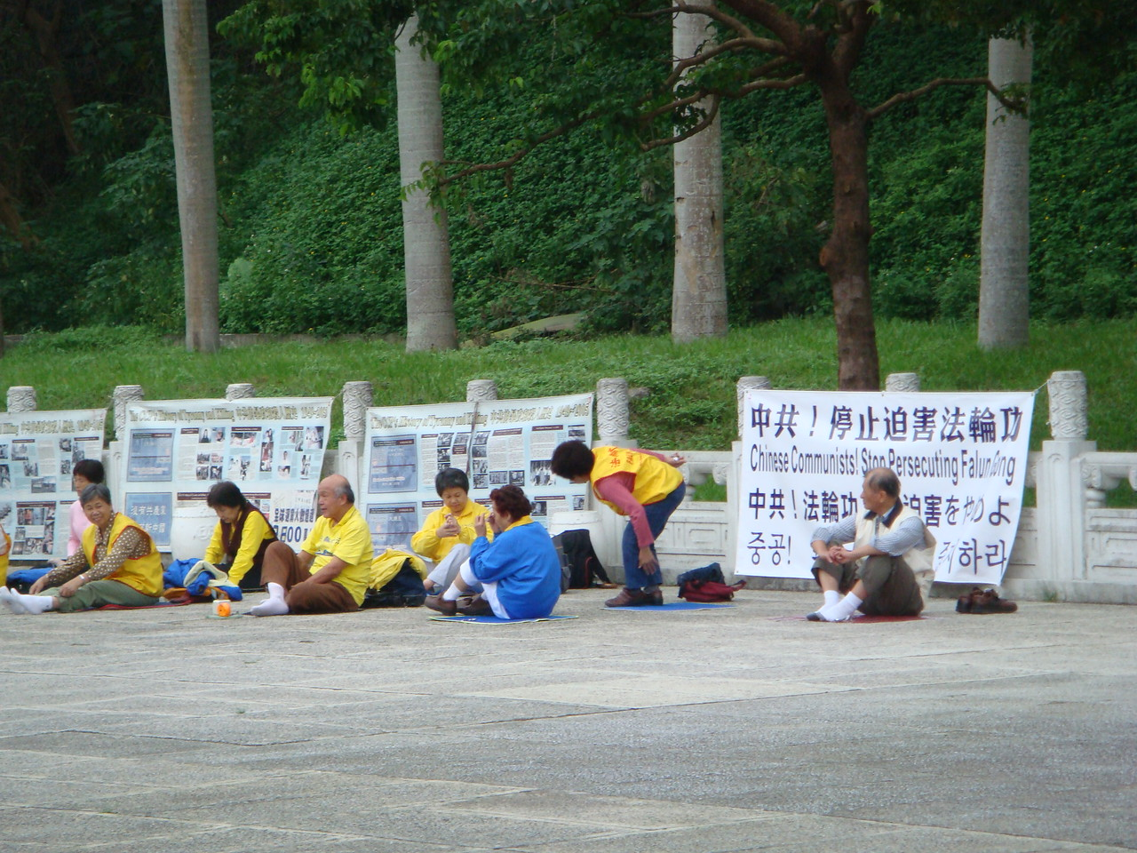 Falun Gong protesters sitting next to signs - Taipei, Taiwan