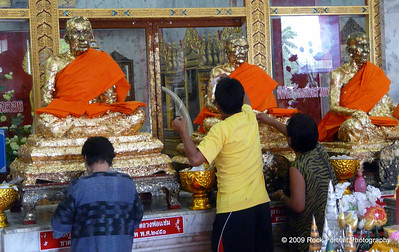 Worshippers stick gold pieces of paper onto these statues of the three monks guarding this temple.