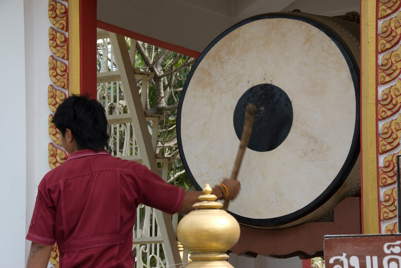 Man banging on a large drum - Ayutthaya, Thailand