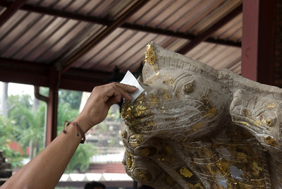Applying gold foil in a statue in Ayutthaya, Thailand