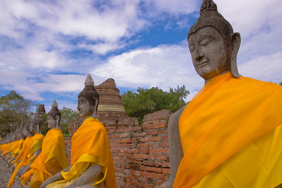Row of Buddhas in orange robes at Ayutthaya, Thailand