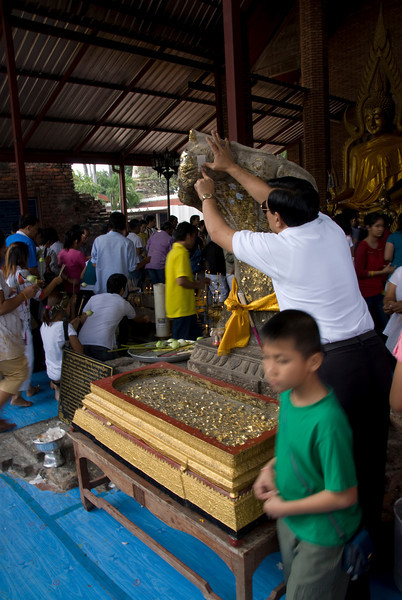 Man applying gold foil on a statue - Ayutthaya, Thailand