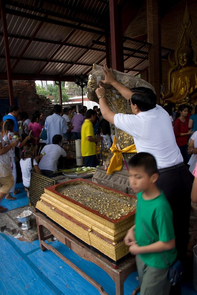 Man applying gold foil on a statue - Ayutthaya, Thailand