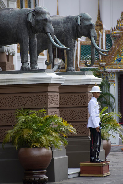 Royal Palace guard standing in between two elephant statues - Bangkok, Thailand