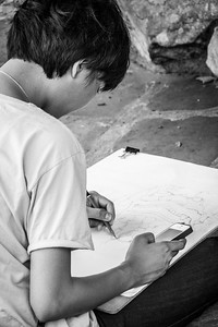 Young female artist enjoying and concentrating on her nice drawing at the stunning Wat Pho.