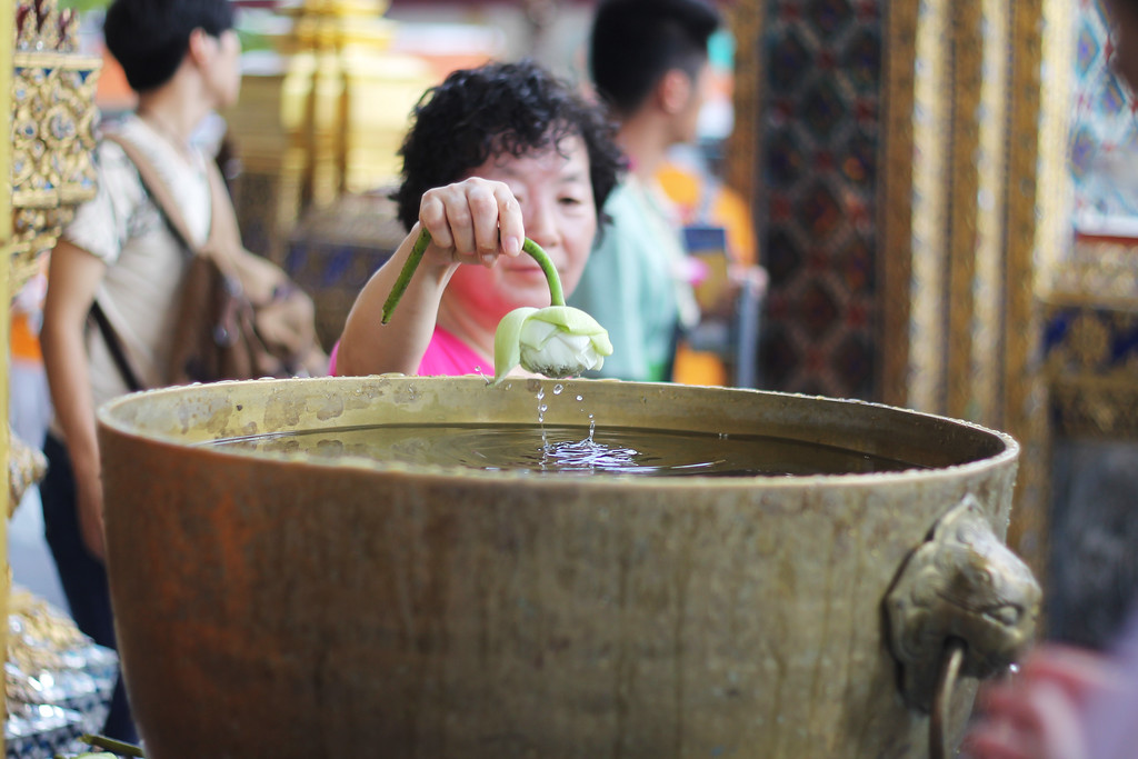 Dipping a lotus flower at the Grand Palace. October 2014