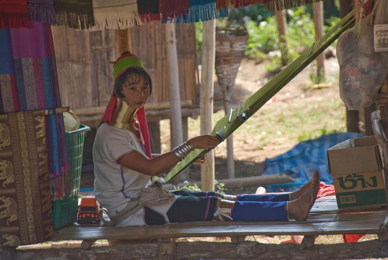Weaving Kayan woman looking at camera - Chiang Mai, Thailand