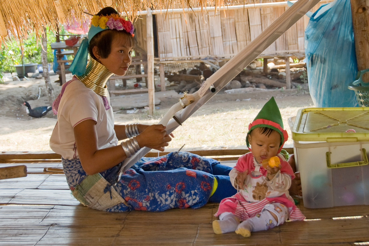 Kayan woman weaving as child plays with toy - Chiang Mai, Thailand