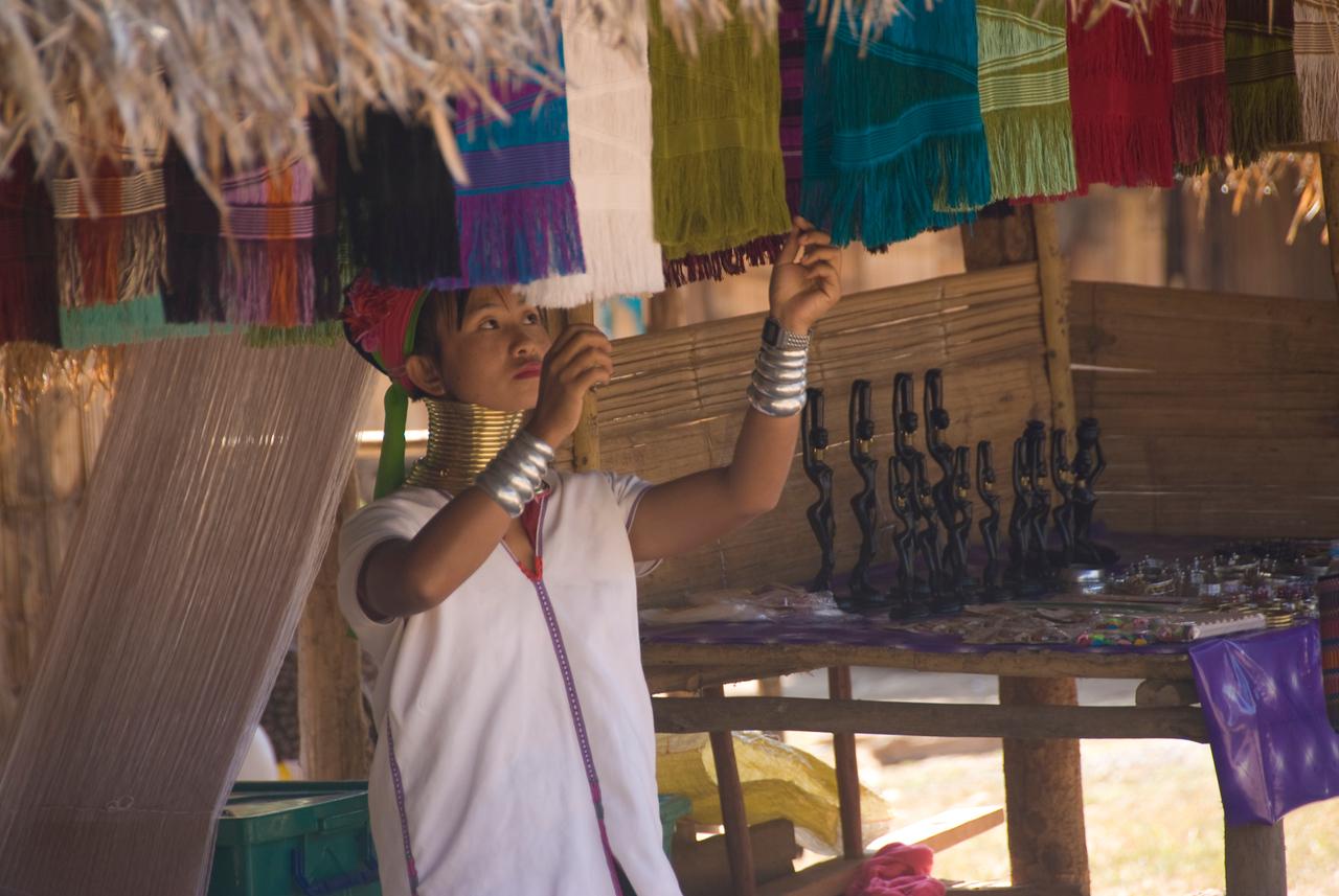 Kayan woman hanging weaved fabrics- Chiang Mai, Thailand