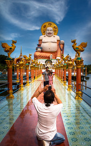 Life scene around the intriguing Wat Plai Laem Temple showing here in the background the fat laughing Chinese Buddha.