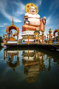 Stunning reflection of the fat laughing Chinese Buddha. As a matter of fact, in Chinese culture, a fat Buddha represents wealth and prosperity. This very impressive statue is 30 meters high and painted in vivid colors like red,  gold, blue.