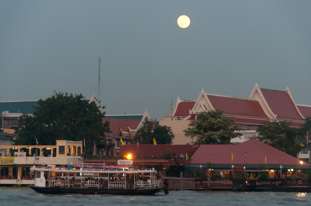 Full moon above the river and skyline in Thailand
