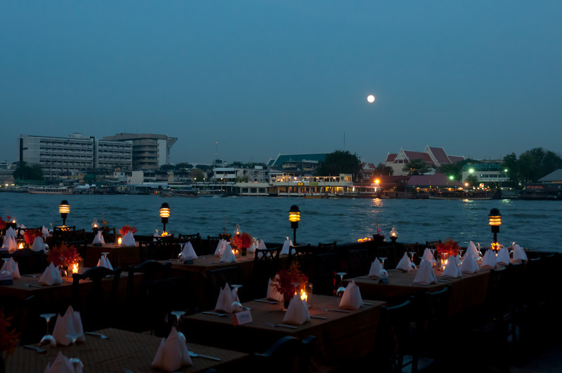 Beautiful table setting overlooking the river, moon and skyline - Thailand