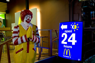 Ronald McDonald next to 24-hour sign in McDonald's Phuket branch