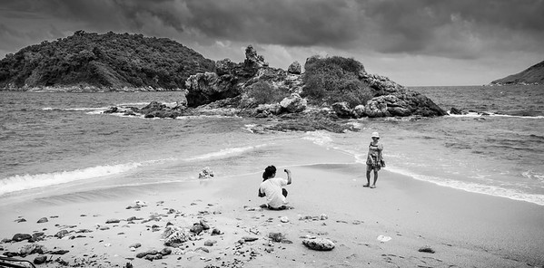 Touching life scene showing a young father holding his baby in one hand and picturing his wife with the other hand on the dreamy Ya Nui beach.