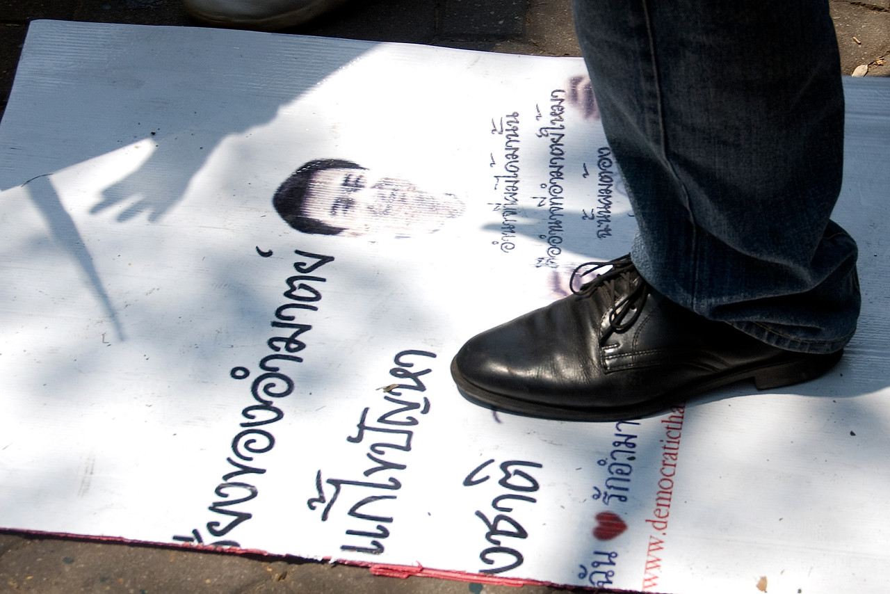Black shoes stomping on protest sign at Red Shirt Protest in Thailand