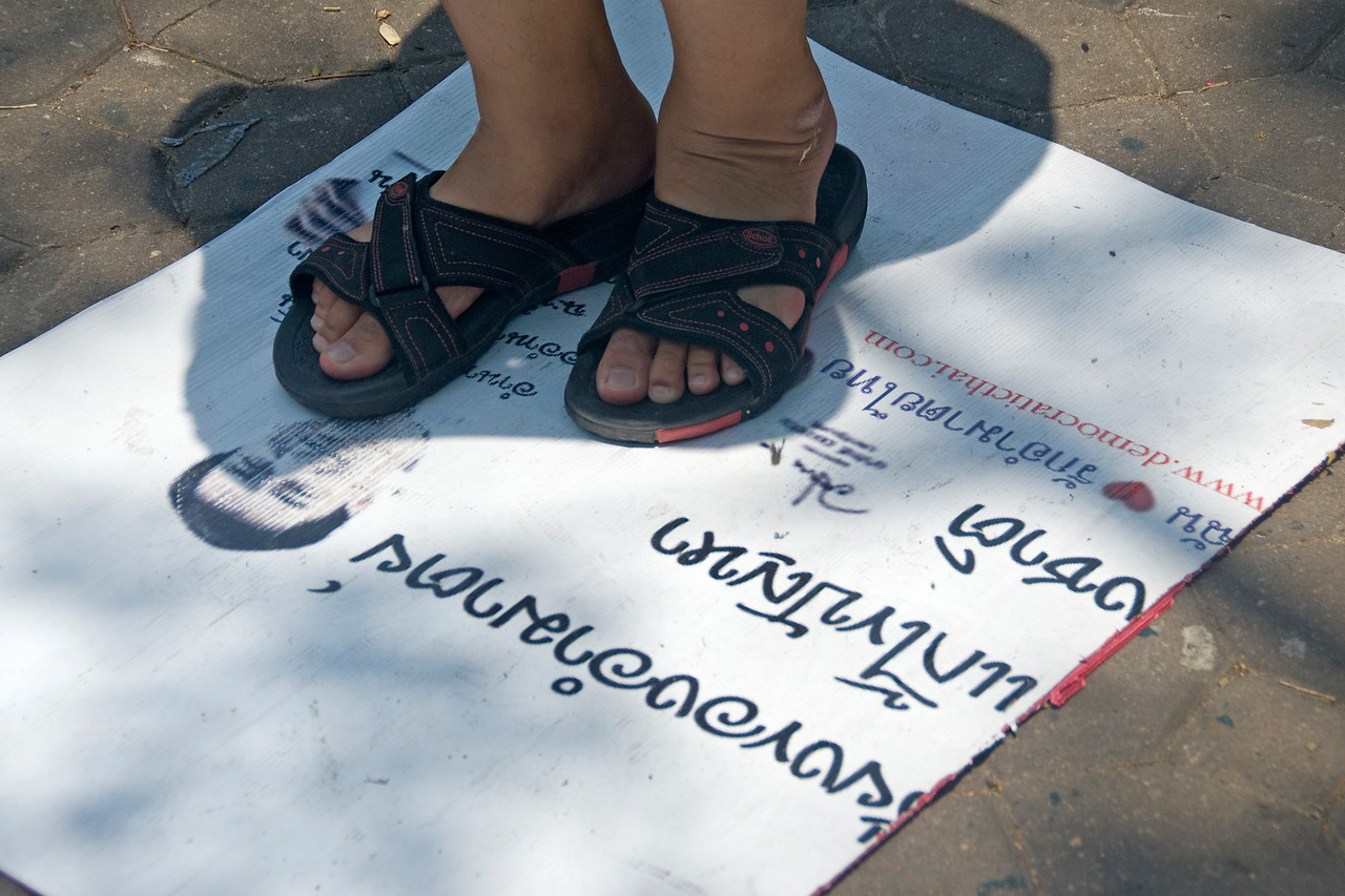 Close-up of feet and protest sign during Red Shirt Protest in Thailand
