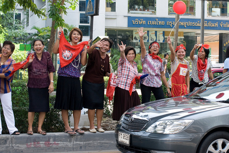 Women waving and smiling to the camera during Red Shirt Protest in Thailand
