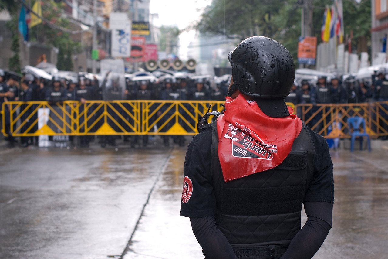 Red shirt protester standing in front of police  barricade - Thailand